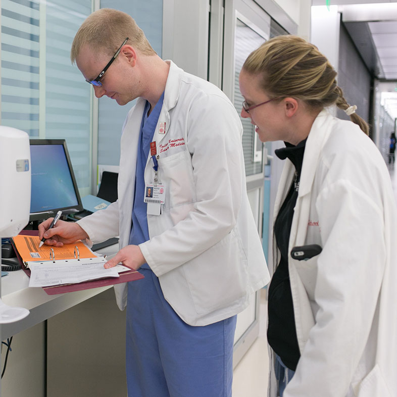 Two students reviewing a patient's chart.