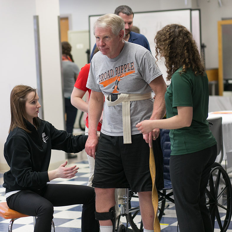 Two physical therapy students helping a wheelchair bound guy walk.