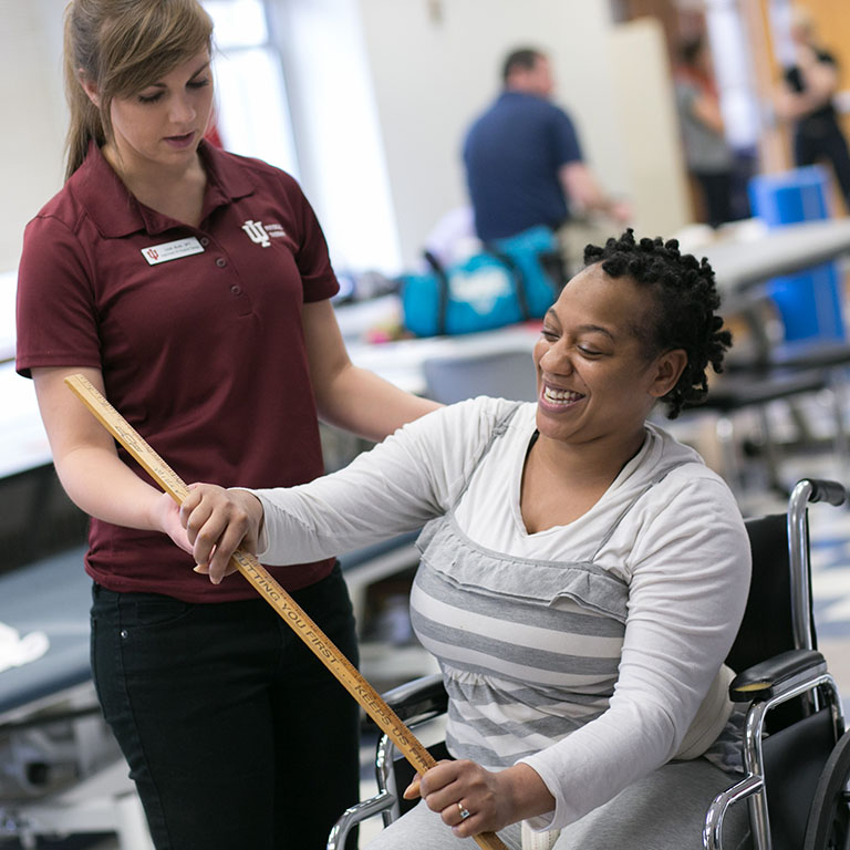 A student helping a woman in a wheelchair do excersizes.