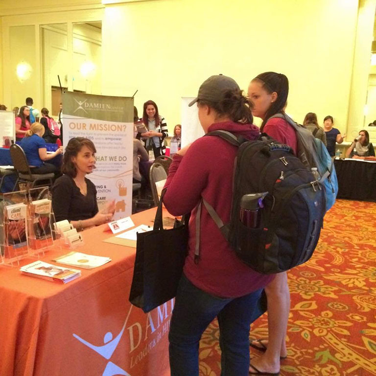 Two students talking to a company representative at the HLS Expo
